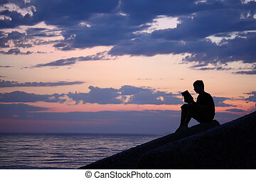 Silhouette guy sitting on breakwater in evening near sea,...