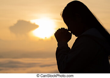 Silhouette hand girl praying at sunset