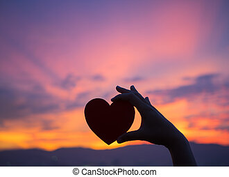 Silhouette hand holding beautiful heart during sunset background. Happy, Love, Valentine's day idea, sign, symbol, concept.