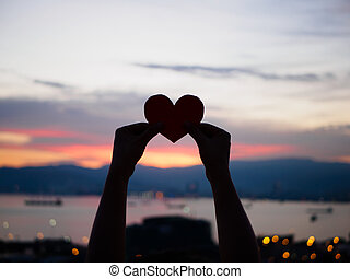 silhouette hand is raising the red paper heart