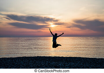 silhouette happiness man on the sunrise beach