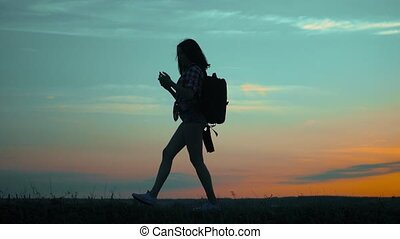 silhouette hiker girl traveler with smartphone navigation...