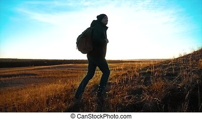 Silhouette hiker man lifestyle of backpacker. steadicam motion video sunlight sunset person side view walking toward successful. lonely man with sunset background. Travel and success concept the adventure