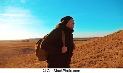 Silhouette hiker man of backpacker. steadicam motion video lifestyle sunlight sunset person side view walking toward successful. lonely man with sunset background. Travel and success concept the adventure