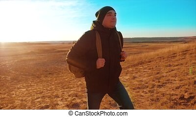 Silhouette hiker man of backpacker. steadicam motion video sunlight lifestyle sunset person side view walking toward successful. lonely man with sunset background. Travel and success concept the adventure