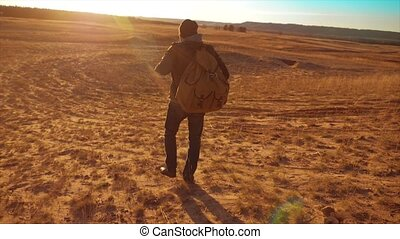 Silhouette hiker man of backpacker. steadicam motion video sunlight sunset person side view walking toward successful. lonely man with sunset lifestyle background. Travel and success concept the adventure