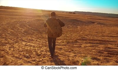 Silhouette hiker man of backpacker. steadicam motion video sunlight sunset person side view walking toward successful. lonely man with lifestyle sunset background. Travel and success concept the adventure