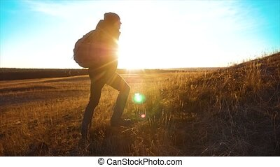 Silhouette hiker man of lifestyle backpacker. steadicam motion video sunlight sunset person side view walking toward successful. lonely man with sunset background. Travel and success concept the adventure
