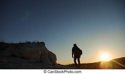 silhouette hiker man tourists climber climbs a mountain....