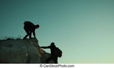 silhouette hiker man tourists hands help climber climbs a...