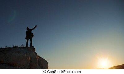 silhouette hiker man tourists hands up climber climbs a...