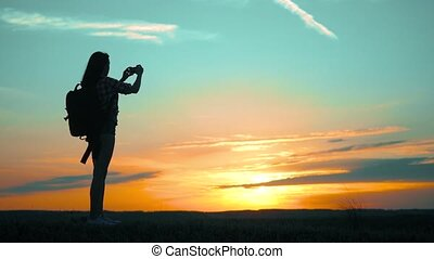silhouette Hipster hiker silhouette girl is shooting video...