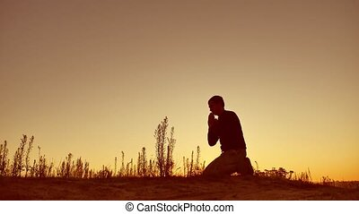 Silhouette illustration of man praying outside at beautiful...