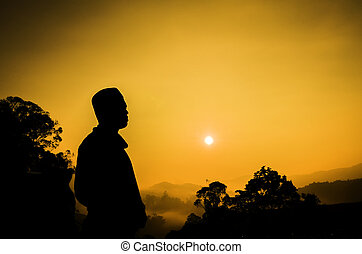 silhouette image of a man standing on top off the hill. sunset sunrise. dark tree as background