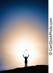 Silhouette image of man with hands raised at a height