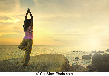 silhouette, jeune femme, pratiquer, yoga, plage, à, sunset.
