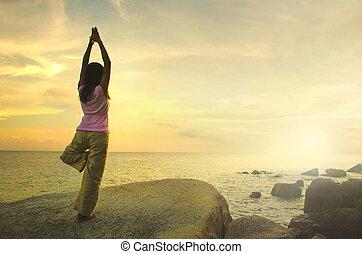 silhouette, jonge vrouw , beoefenen, yoga, op het strand, op, sunset.