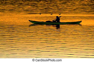Silhouette kayaking at sunset