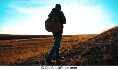 Silhouette lifestyle hiker man of backpacker. steadicam motion video sunlight sunset person side view walking toward successful. lonely man with sunset background. Travel and success concept the adventure