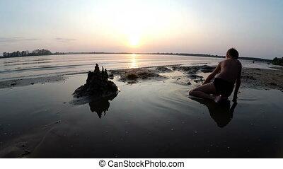 Silhouette Little Boy Builds a Sand Castle at Sunset
