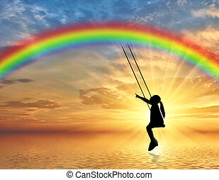 Silhouette, little girl child on a swing rainbow over the sea.