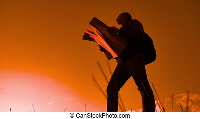 silhouette man as he reads the map, traveling alone On the big rock - outdoor and Holiday,travel concept. tourist travel concept lifestyle