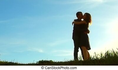 silhouette man circling girl amusement hugs at sunset. Man...