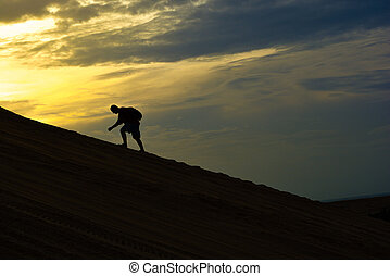 Silhouette man climb the mountain in morning with light sky background