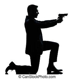 silhouette man kneeling aiming gun - one caucasian spy...