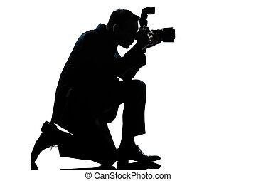 one caucasian man kneeling photographer full length silhouette in studio isolated on white background