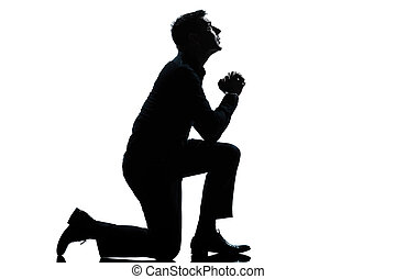 one caucasian man kneeling praying full length silhouette in studio isolated white background