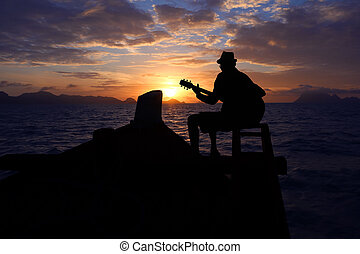 Silhouette man playing a guitar on the boat with blue sky sunrise