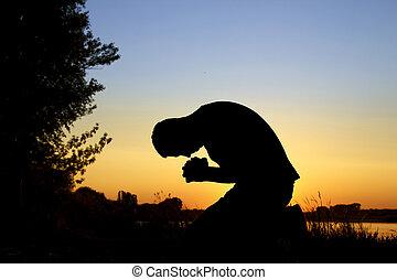 silhouette man praying - silhouette on sunset man praying