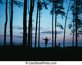 Silhouette man standing in forest rising hands with sea sunset background