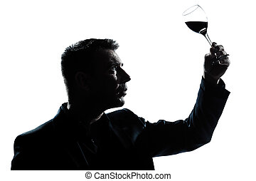 silhouette man tasting looking at his glass of red wine -...