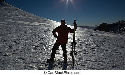 Silhouette man with ski board standing on snow