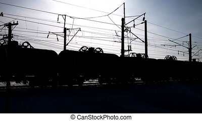 Silhouette, moving the freight train transporting oil,...
