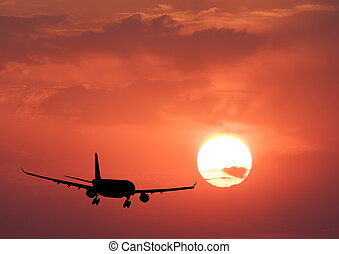 Silhouette of a airplane and colorful sky with sun