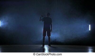 Silhouette of a basketball player throwing a ball.