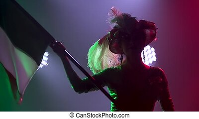 Silhouette of a beautiful actress waving the flag of Italy against the backdrop of bright colored lights and smoke. Theatrical show close up. Slow motion