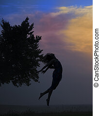 silhouette of a beautiful girl jumping in the sunset
