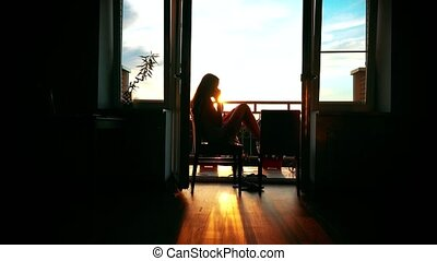 Silhouette of a beautiful girl talking on her cellphone at home.