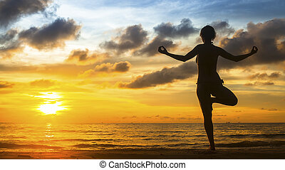 Silhouette of a beautiful yoga woman meditation on the ocean coast during the amazing sunset.
