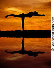 Silhouette of a beautiful Yoga woman with water reflection
