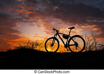 Silhouette of a bicycle during sunset. Sandy meadow. No one.