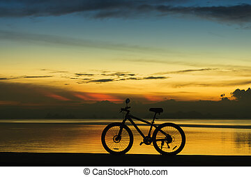 Silhouette of a bike on a lake at twilight.
