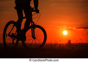 Silhouette of a bike on sky background during sunset -...