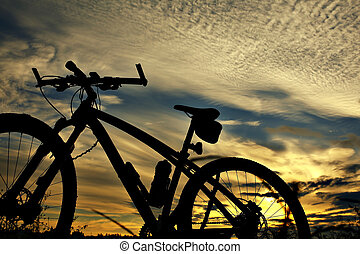 Silhouette of a bike on sky background.