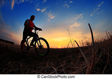 Silhouette of a biker and bicycle on sunset background.