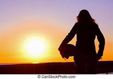 silhouette of a biker girl at sunset